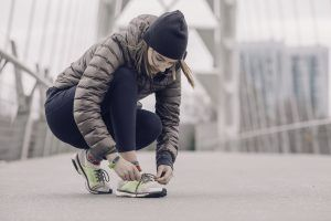 A girl wearing a hat and coat tying the laces of running shoes, as advised by our country PR team.