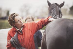 Tracia Bracegirdle strokes a horse, a Childéric saddle technician, who speaks to our equine team.