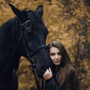 A girl hugging a black horse, an image seen often by the MirrorMePR equestrian PR team.