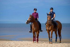 2 horses and their riders on a sunny beach as part of luxury riding holidays.