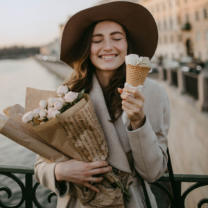 woman wearing a mac carrying flowers and an ice cream